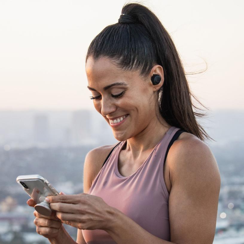 JLab Headphones: #1 True Wireless Headphones under $100 - photo of woman on her phone on adayinnmotherhood.com
